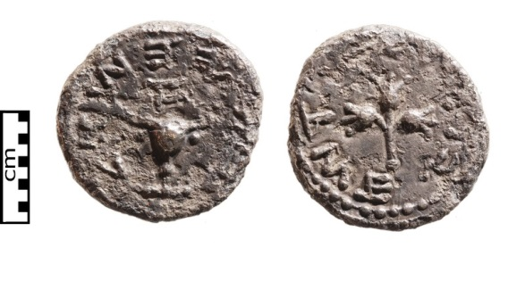 "A rare silver half-shekel coin found in the sifting. Obverse: A chalice from the Temple topped by the letter aleph, meaning ""Year One"". Around it are the words ""half a shekel"". Reverse: A branch with three pomegranates surrounded by the words ""Holy Jerusalem"". These coins were used for paying the annual Temple tax according to the Biblical commandment in Exodus 30:13-15."